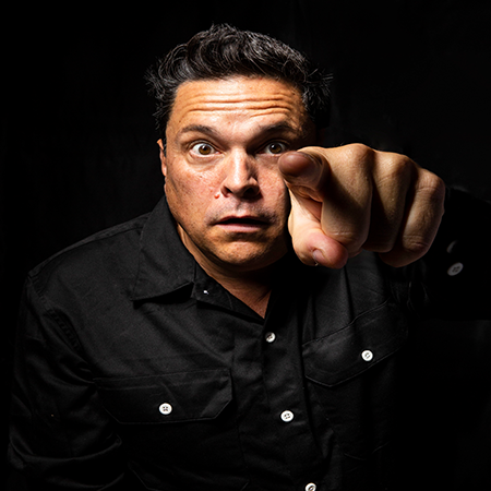 Dom Joly performing at a show, Holiday Snaps - Travel and Comedy in the Danger Zone